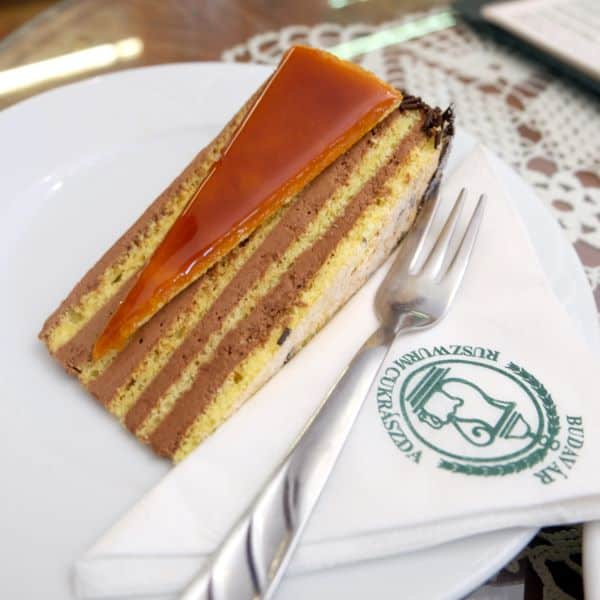 Dobos Torte on a white plate with fork at Ruszwurm Cafe, Buda, Budapest, Hungary