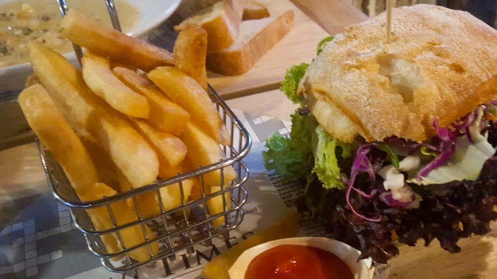 burger with brioche bun, lettuce, basket of fries