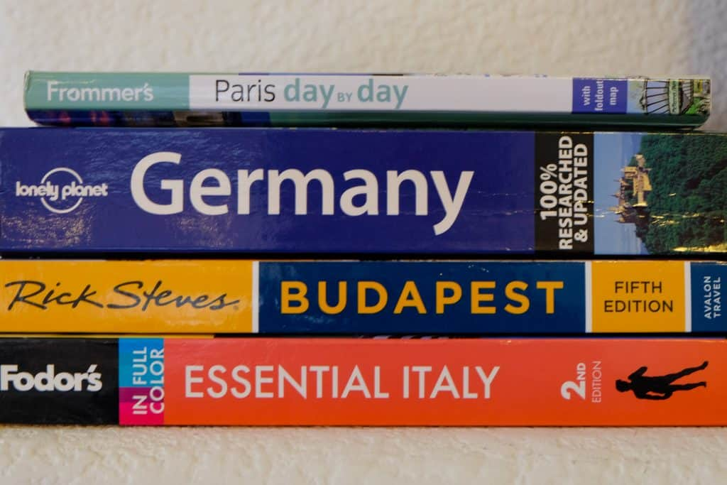Stack of travel guidebooks for Italy, Budapest, Germany and Paris