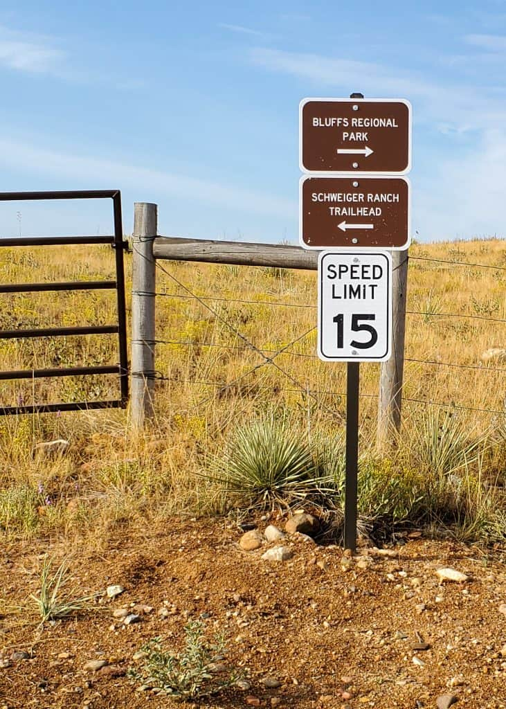 Signpost on the East/West Regional Trail with speed limit 15 and signs pointing to Bluffs Regional Park and Schweiger Ranch Trailhead