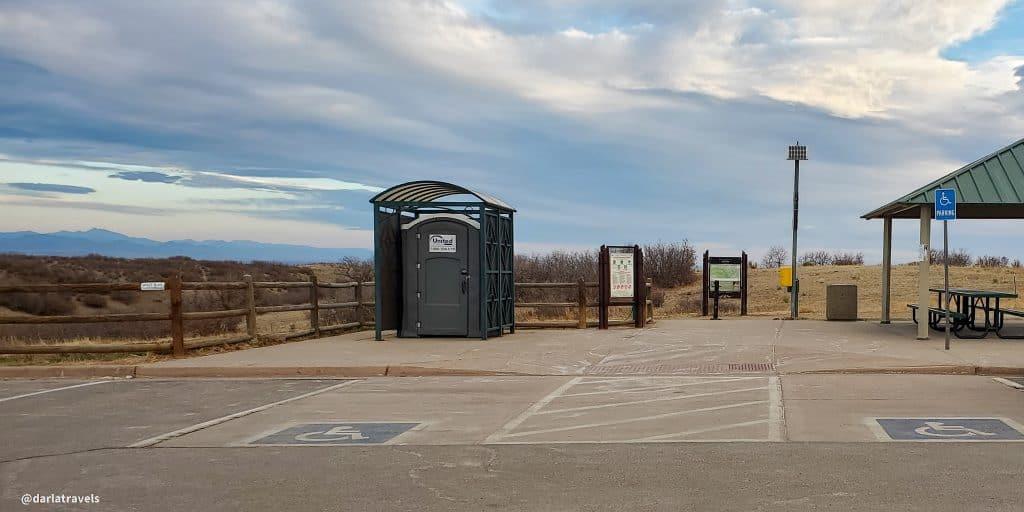 Grigs Road Trailhead, Douglas County Colorado shows a portable restroom, handicap parking and picnic shelter