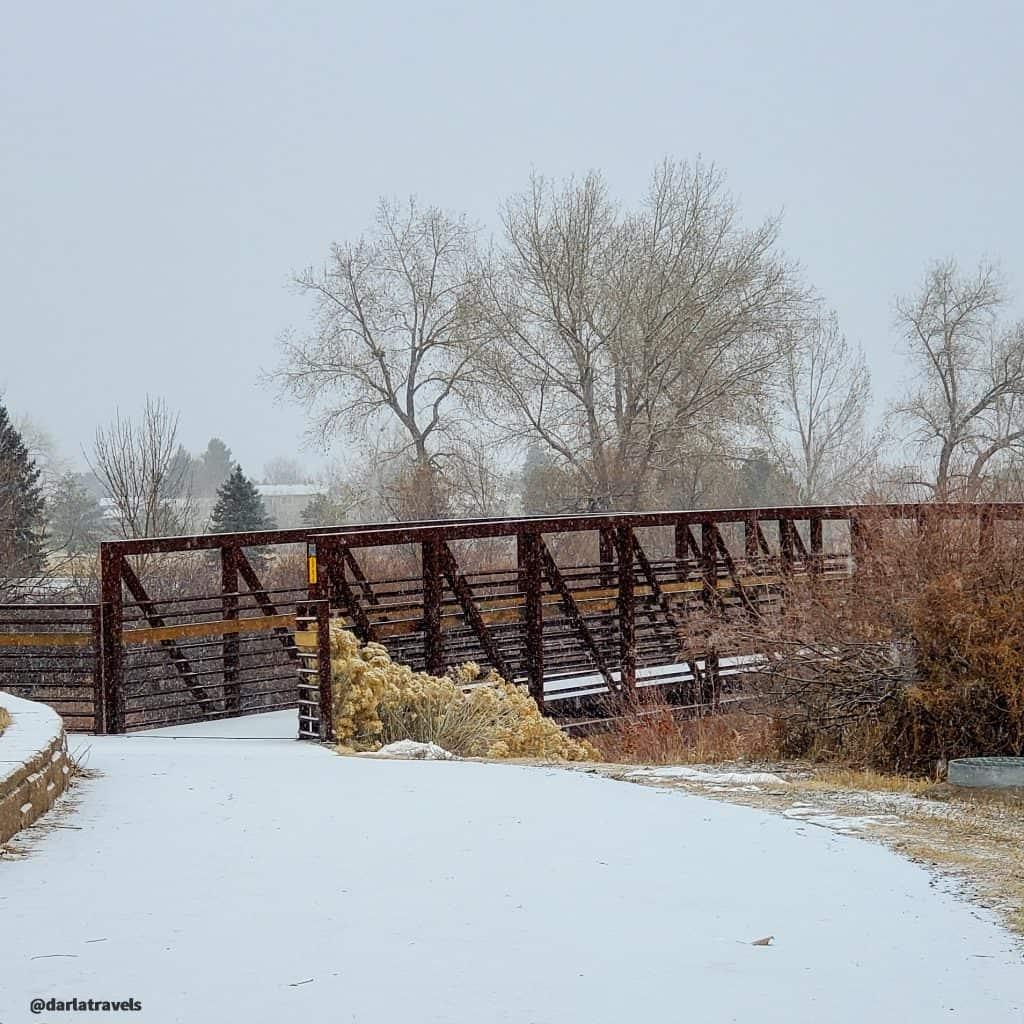 Willow Creek Trail pedestrian bridge in Lone Tree on a snowy morning near Cook Creek Park