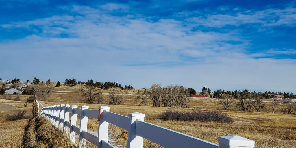 View to the northeast from the extension of the Sulphur Gulch Trail. white fence prairie grass