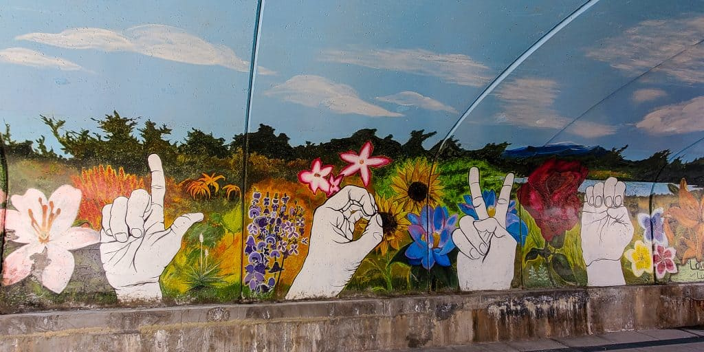"""""""Love Others"""" mural by Lutheran HS, hands spelling LOVE in American sign language, against a landscape backdrop of wildflowers"""