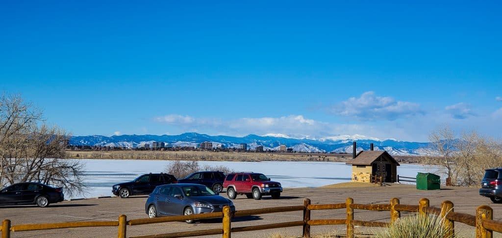 Parking lot with cars and restroom building at Cherry Creek State Park, Aurora, Colorado, frozen reservoir, Rocky Mountains in the distance