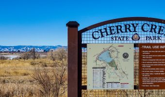 Cherry Creek State Park sign with Rocky Mountains in the background