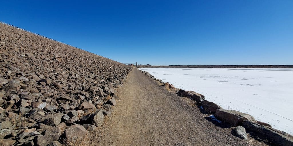 Dam Trail in Cherry Creek State Park. Dam on the left of trail, frozen reservoir on the rigth