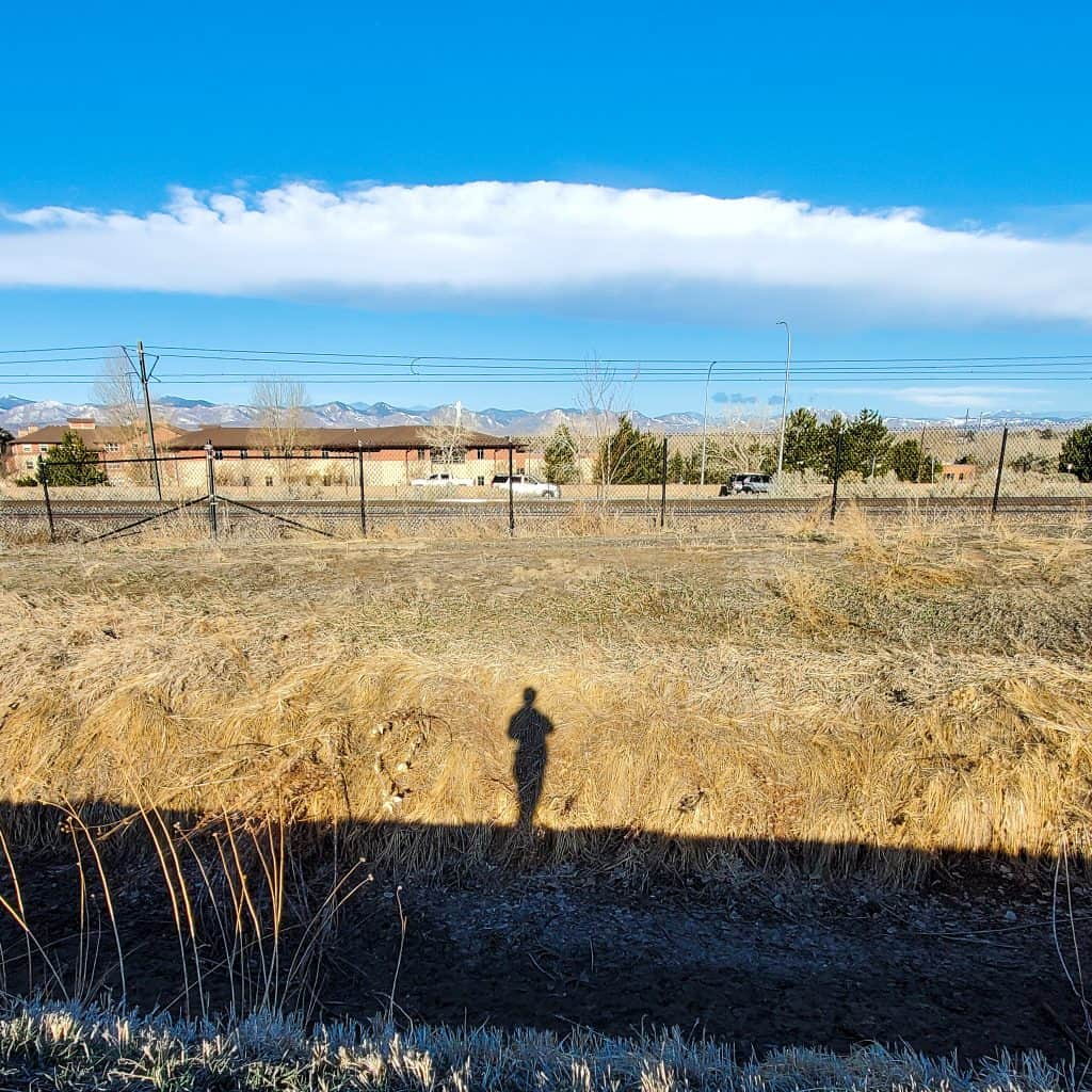 Shadow of person looking across railroad tracks and road with Rocky Mountains in the distance.