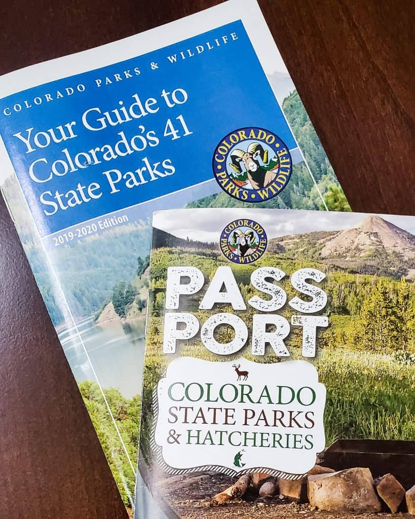 Covers of Colorado Parks and Wildlife's publications Colorado State Parks & Hatcheries Passport, and Your Guide to Colorado's 41 State Parks