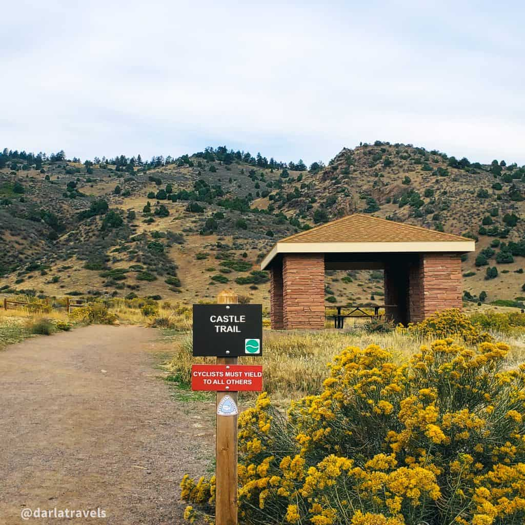 View of the Castle Trail, Trail sign, and picnic shelter at the east trailhead of Mount Falcon Park, in Morrison, Colorado.