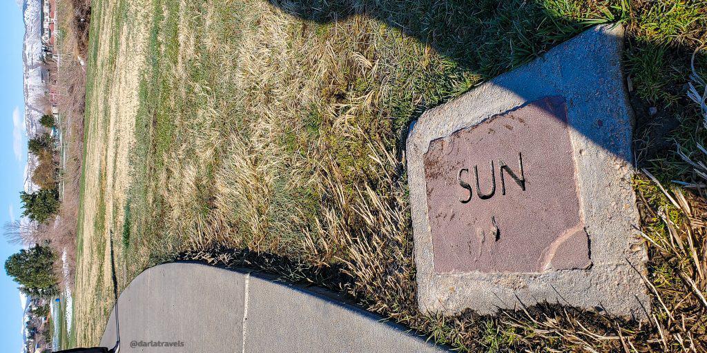 Scale model solar system sun marker next to Van Bibber Creek Trail in Jefferson County, Colorado