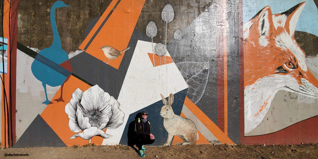 Yulia Avgustinovich mural on the Sand Creek Regional Greenway with animals, birds, plants, and trees